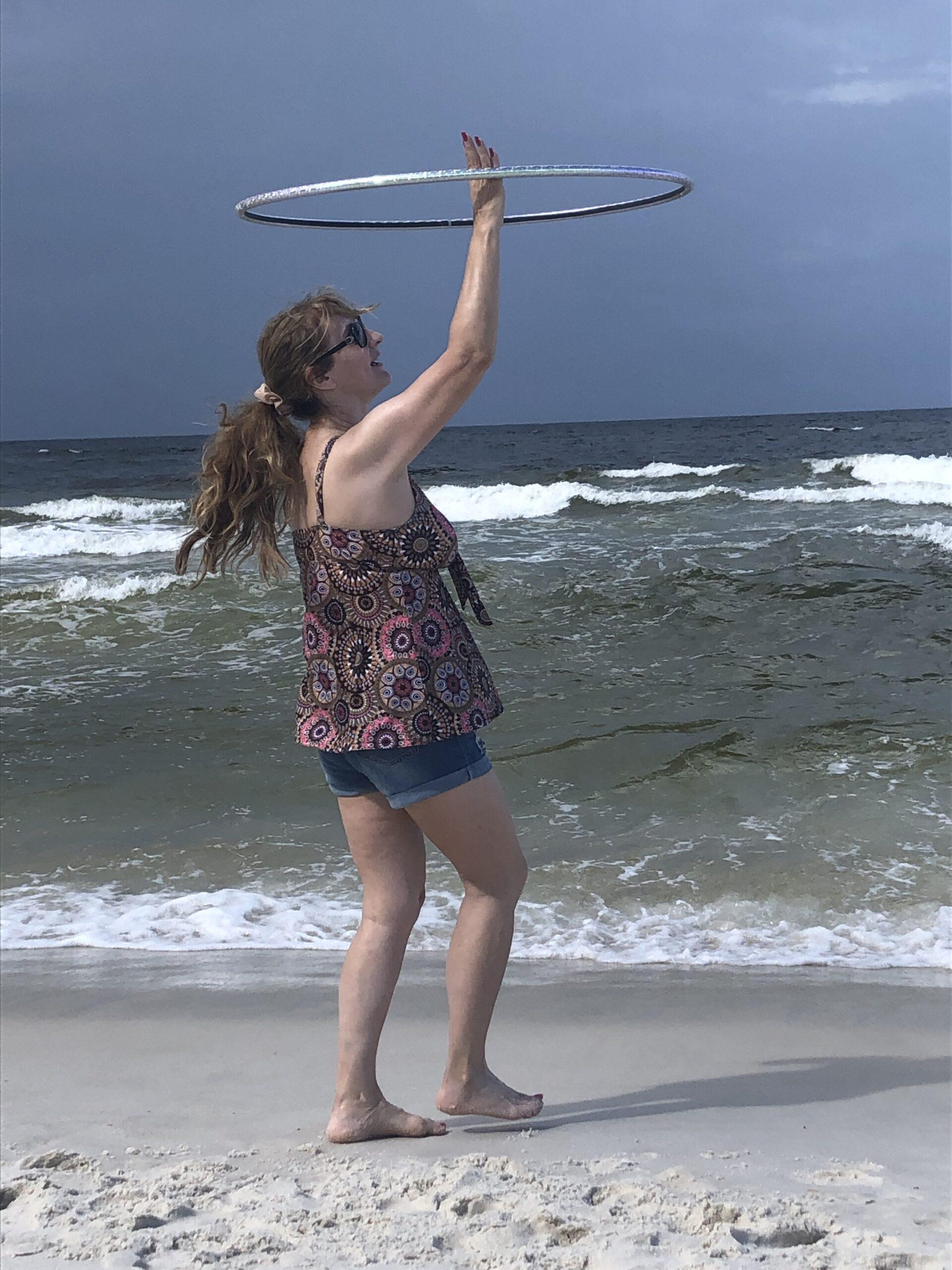 Woman spinning hula hoop on sandy beach