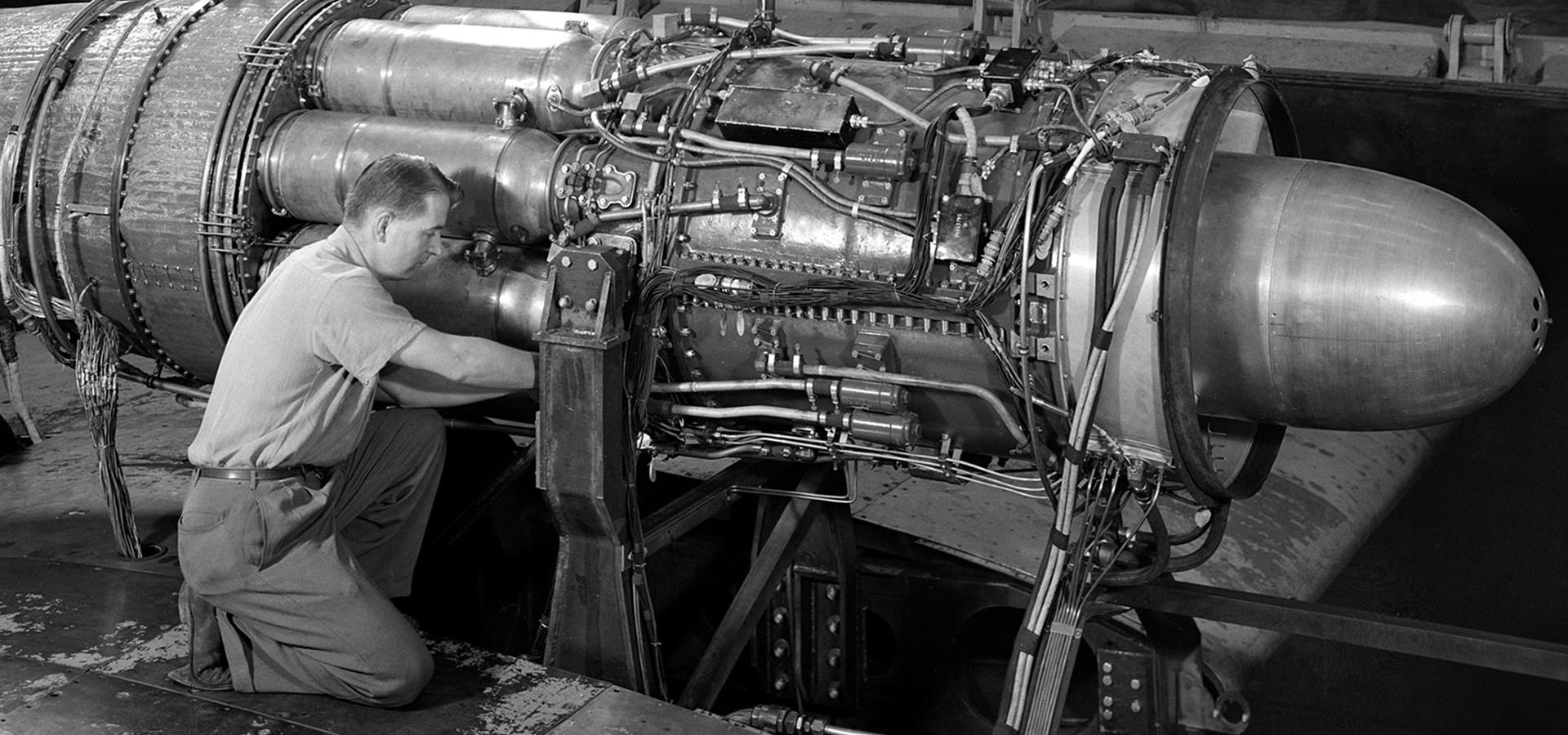 Guy kneeling working on a jet engine