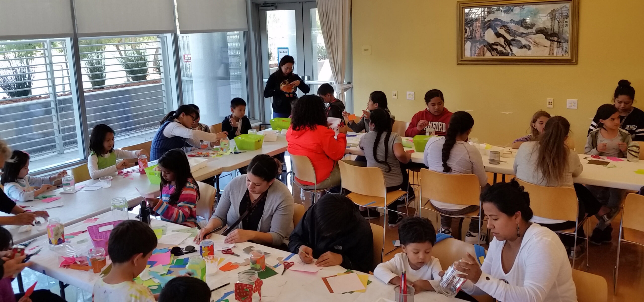 Parents and kids around long tables working on crafts