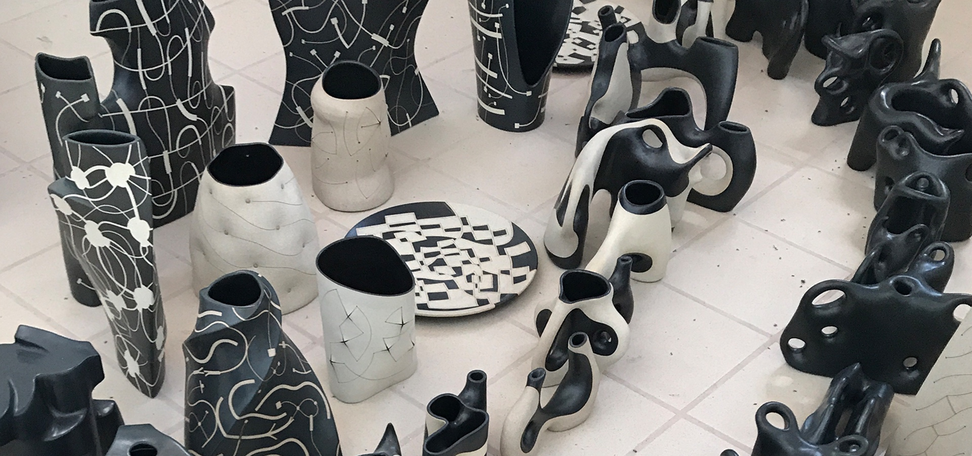 Black and white ceramics laid on the floor as seen from above