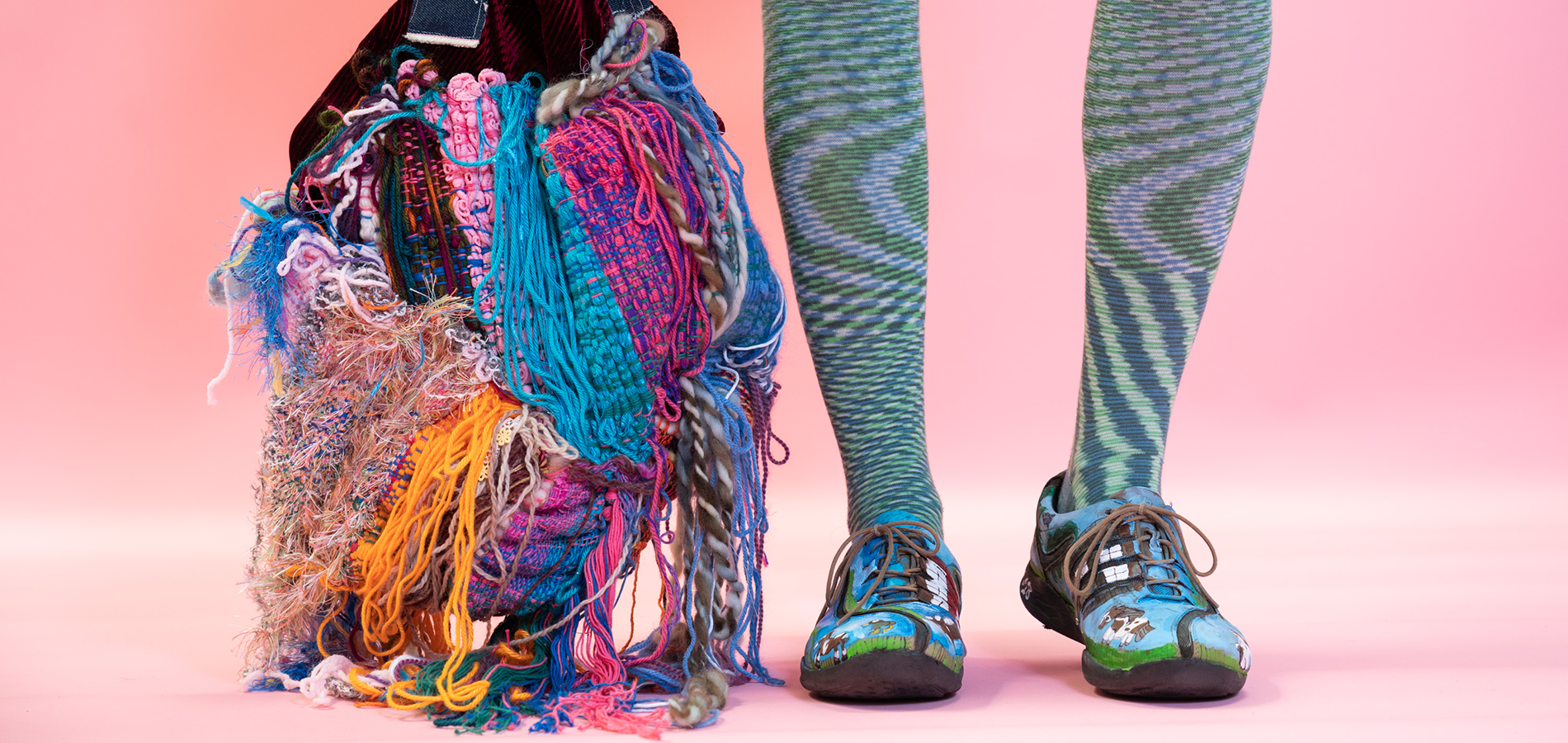 Colorful textile bag hanging down next to legs and shoes