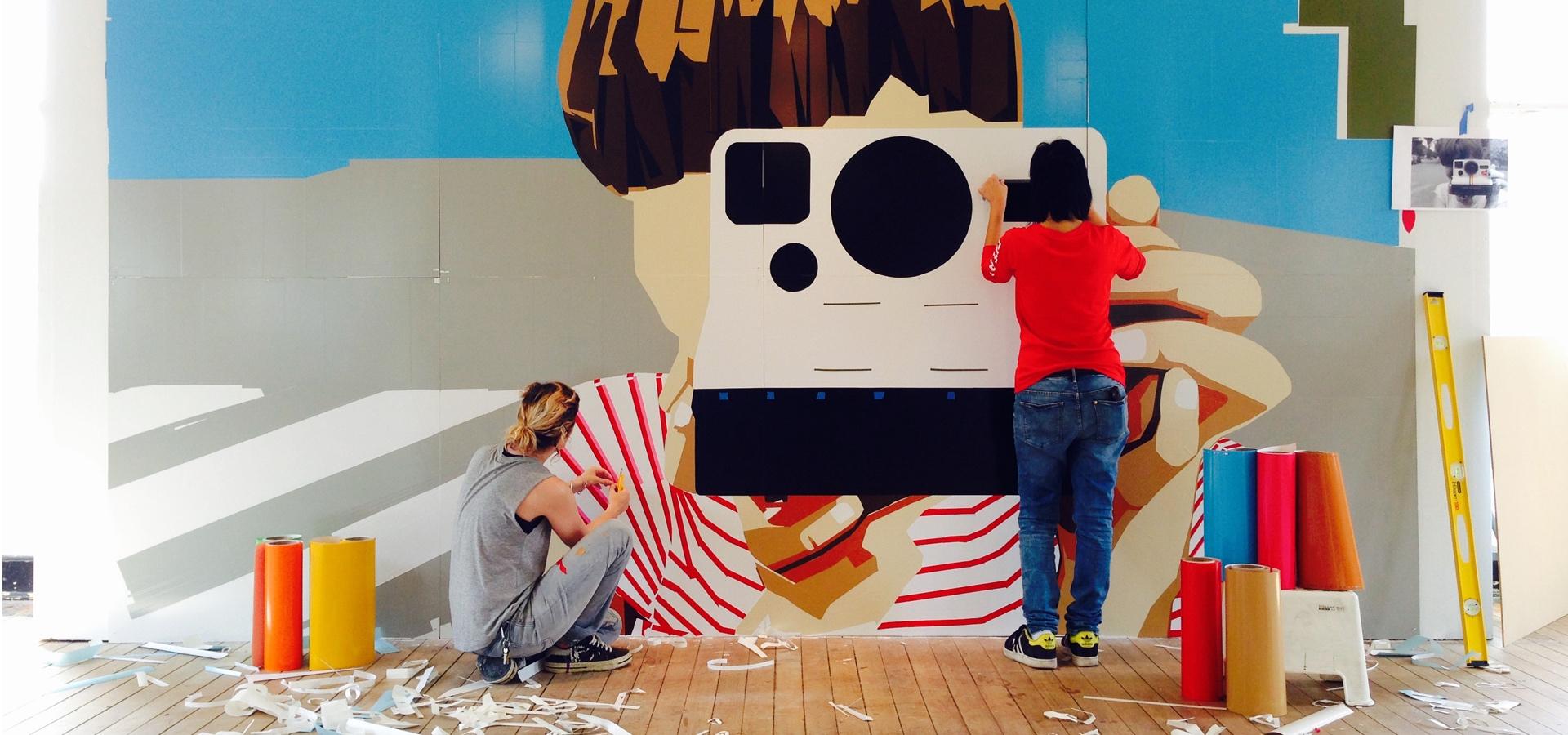 Artists installing cut vinyl wall