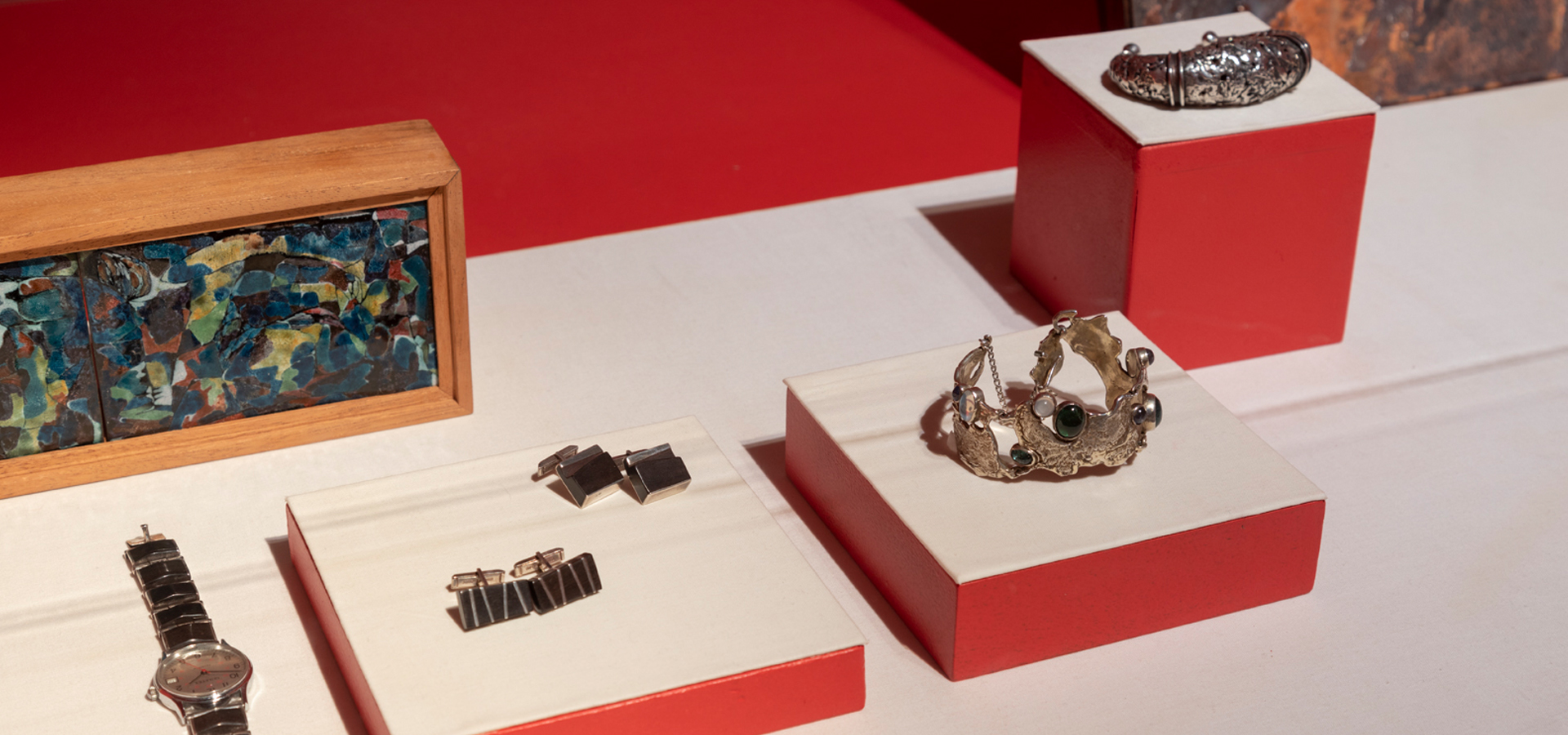 Jewelry on display in gallery with red walls as backdrop