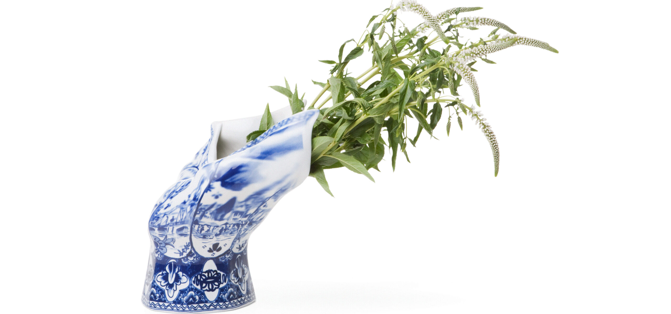 Blue and White ceramic vase bent toward right with greenery sticking out