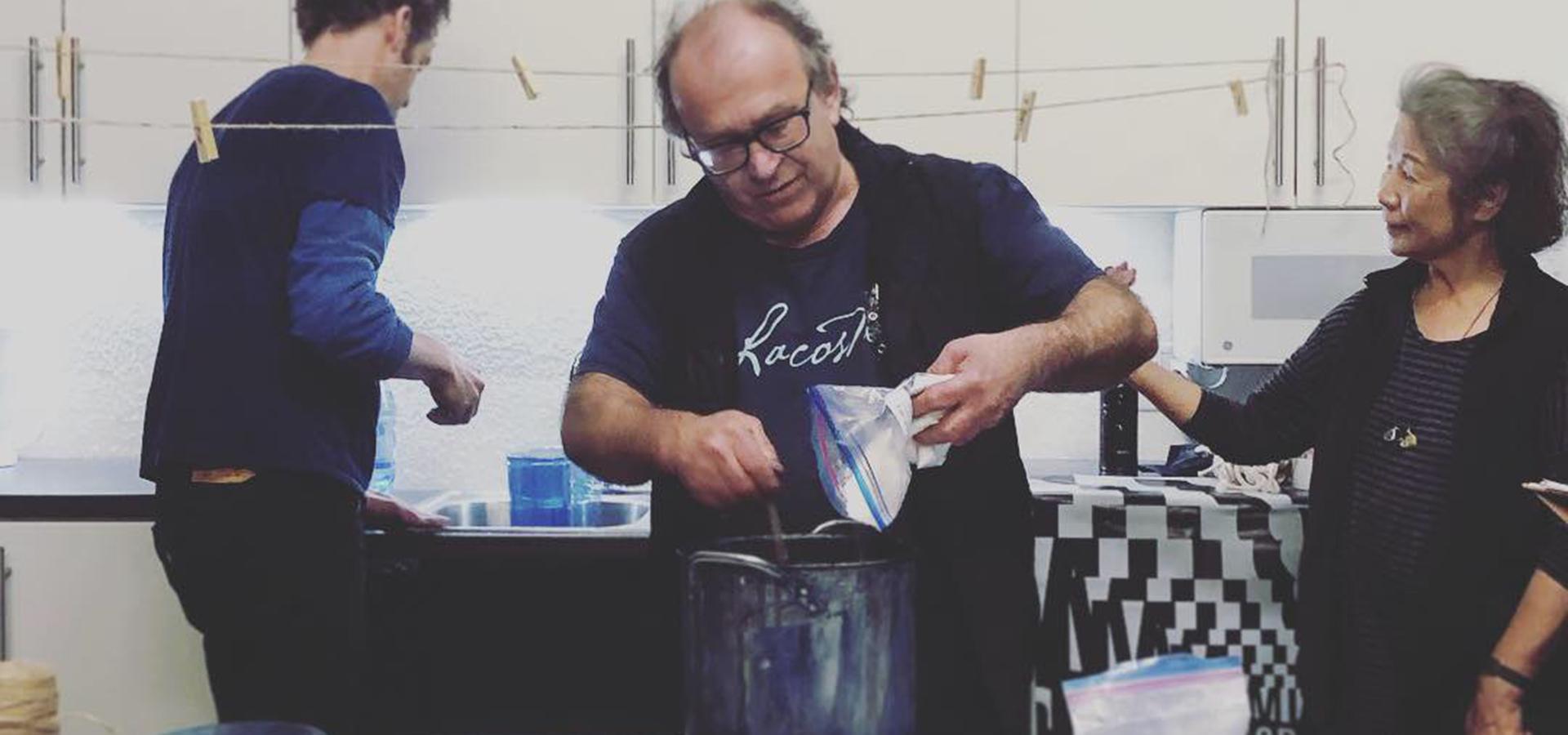 Guy mixing indigo paint for artist workshop