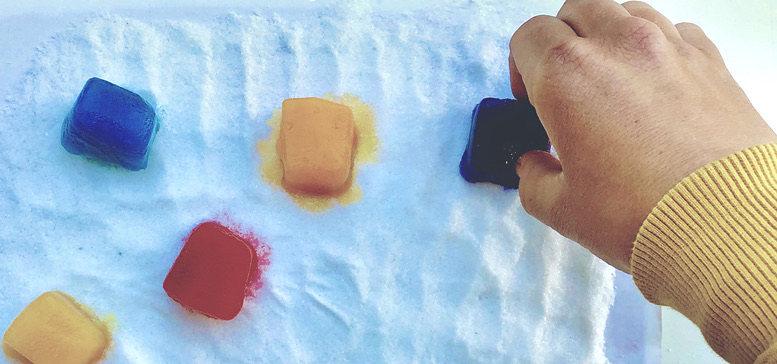 Color ice cubes on and hand reaching out to one white cloth