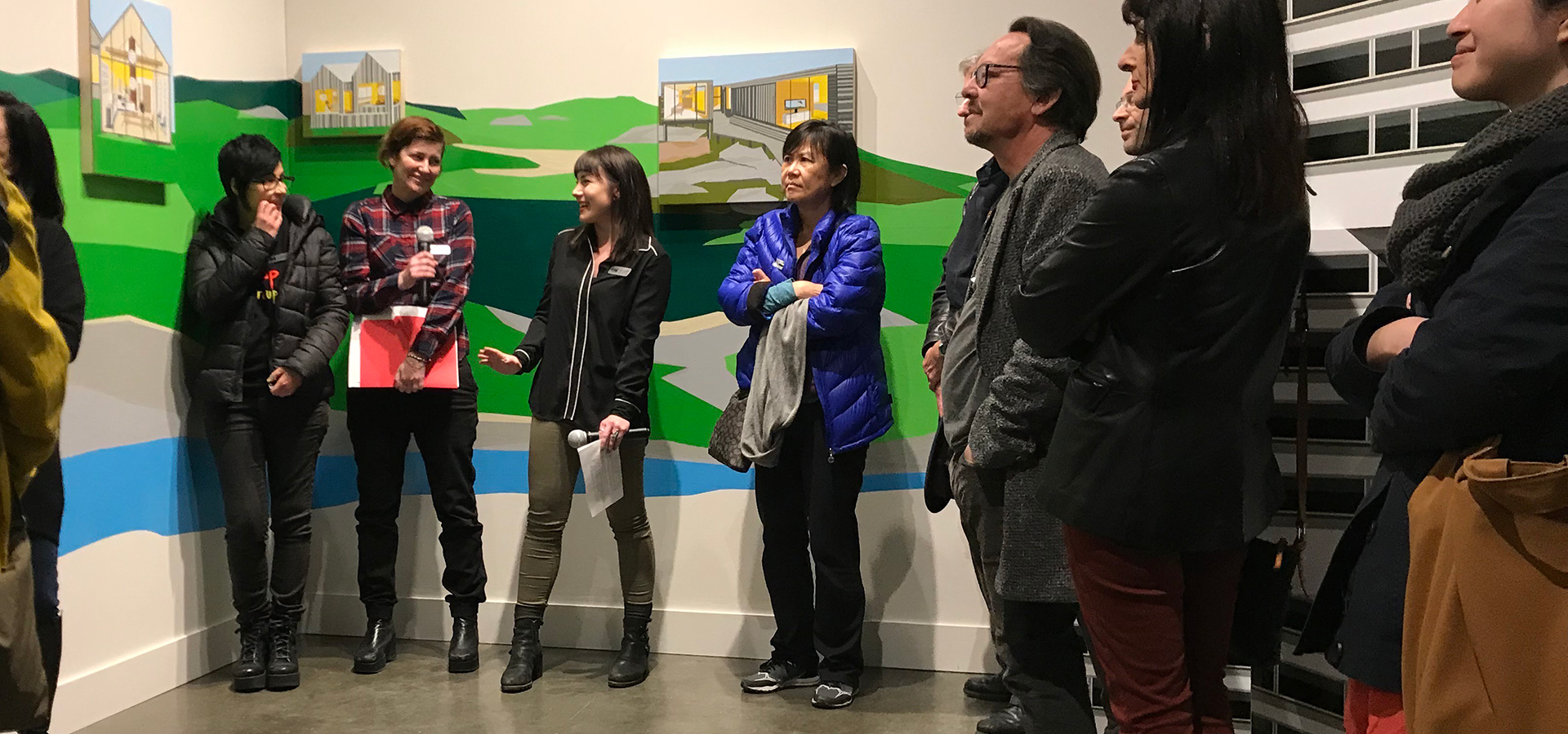 Group of people standing and listening to artist talk