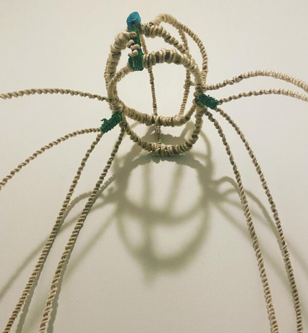 A headdress made of hair, wire, and beads.