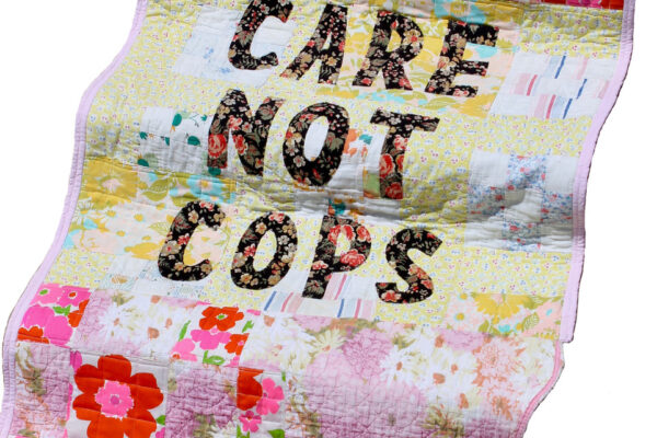 Quilt that says Care not Cops