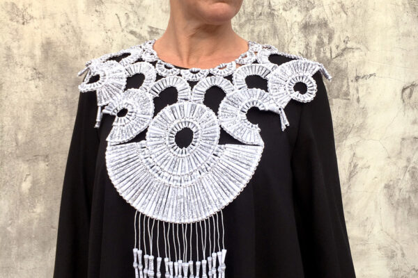 A woman wears an ornate lace-looking white collar.