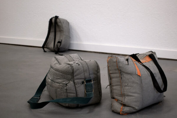 Backpacks and bags cast in concrete.