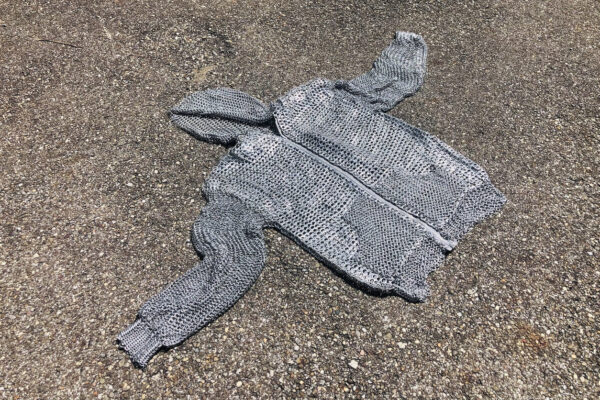 A hooded sweatershirt woven like chainmail with aluminum can tabs.