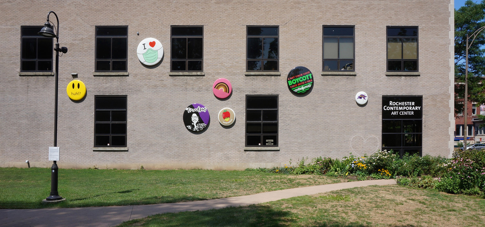 large scale button/pins mounted on facade of concrete wall with windows