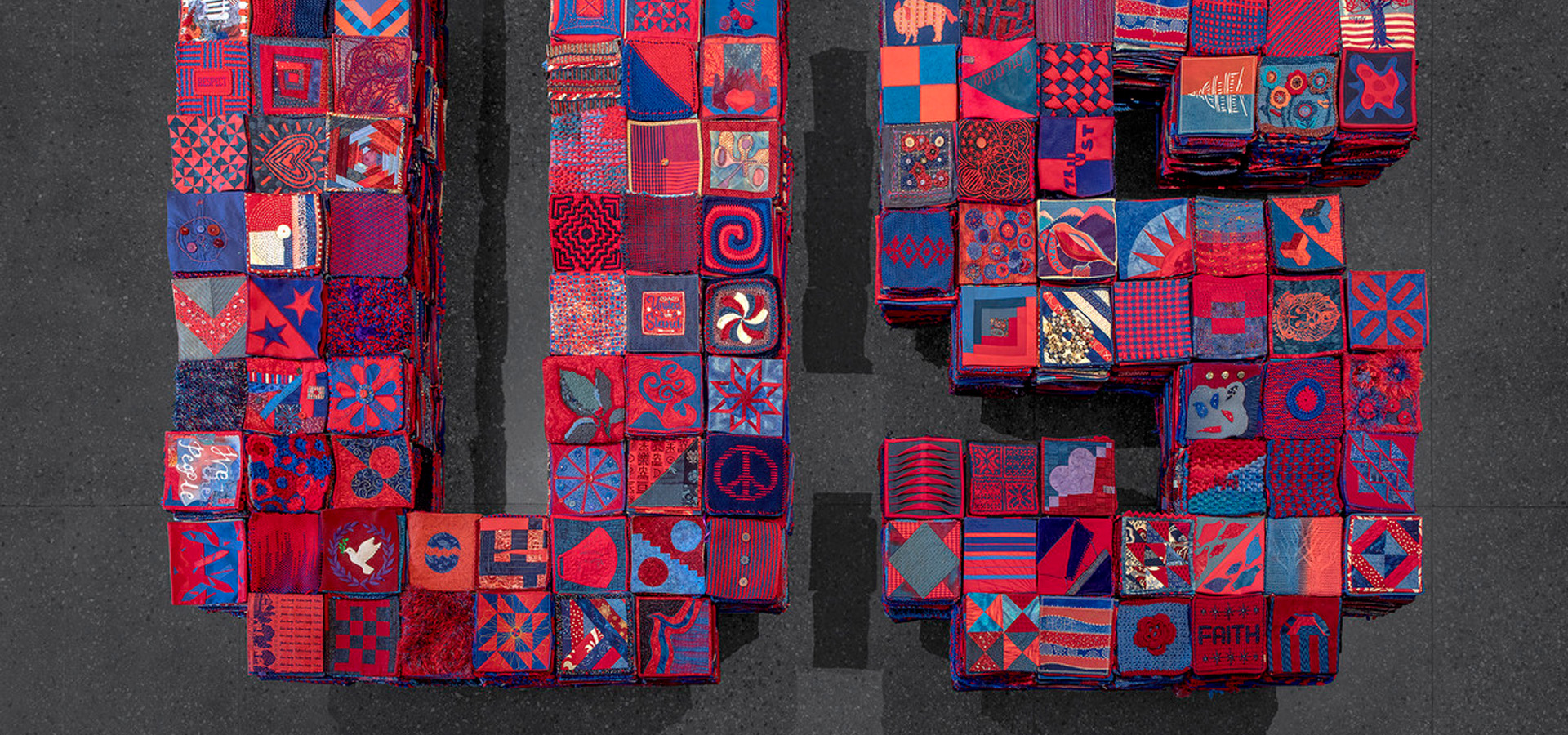 A quilted collage of squares in red, blue, and pink.