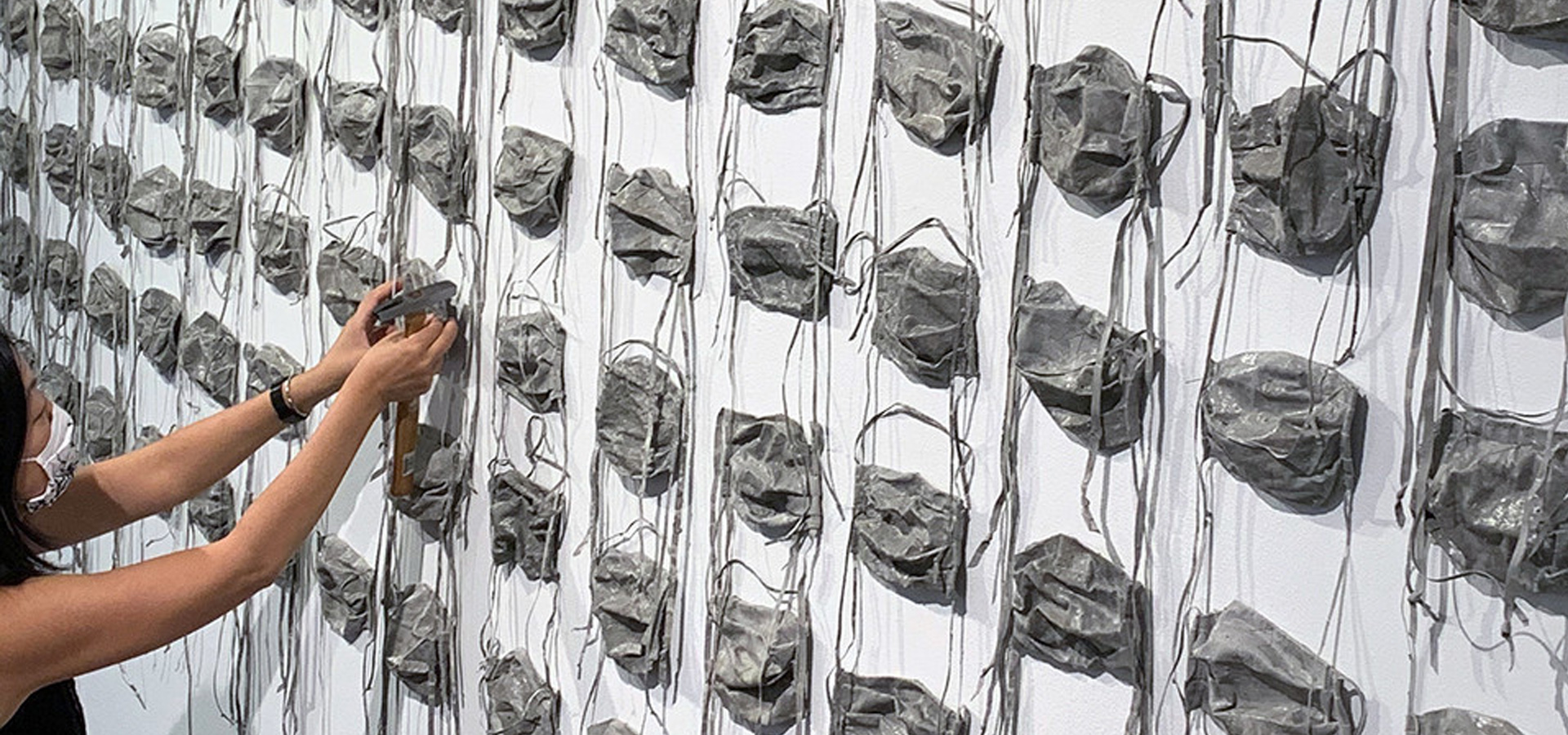 Rows of concrete surgical face masks mounted on a wall.