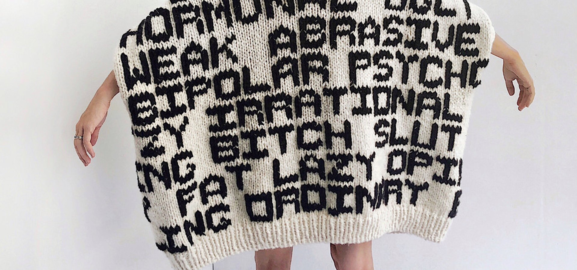 A beige sweater with phrases knitted into it in black yarn.