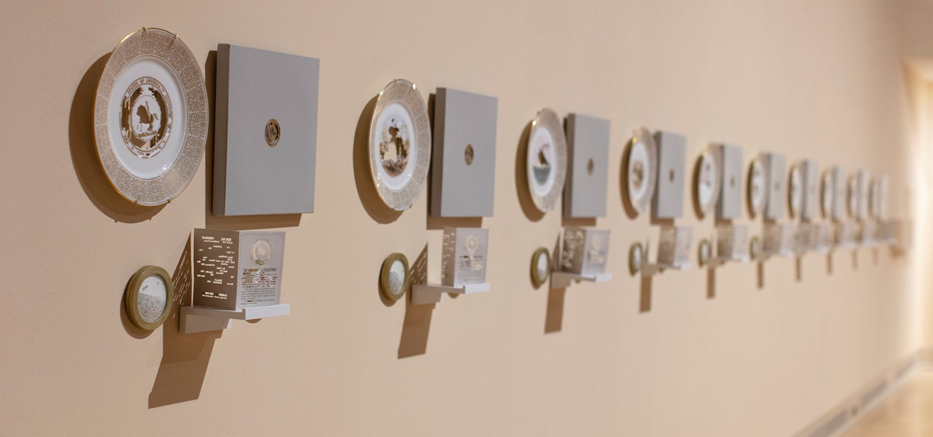 A row of porcelain plates and plaques mounted on a wall.