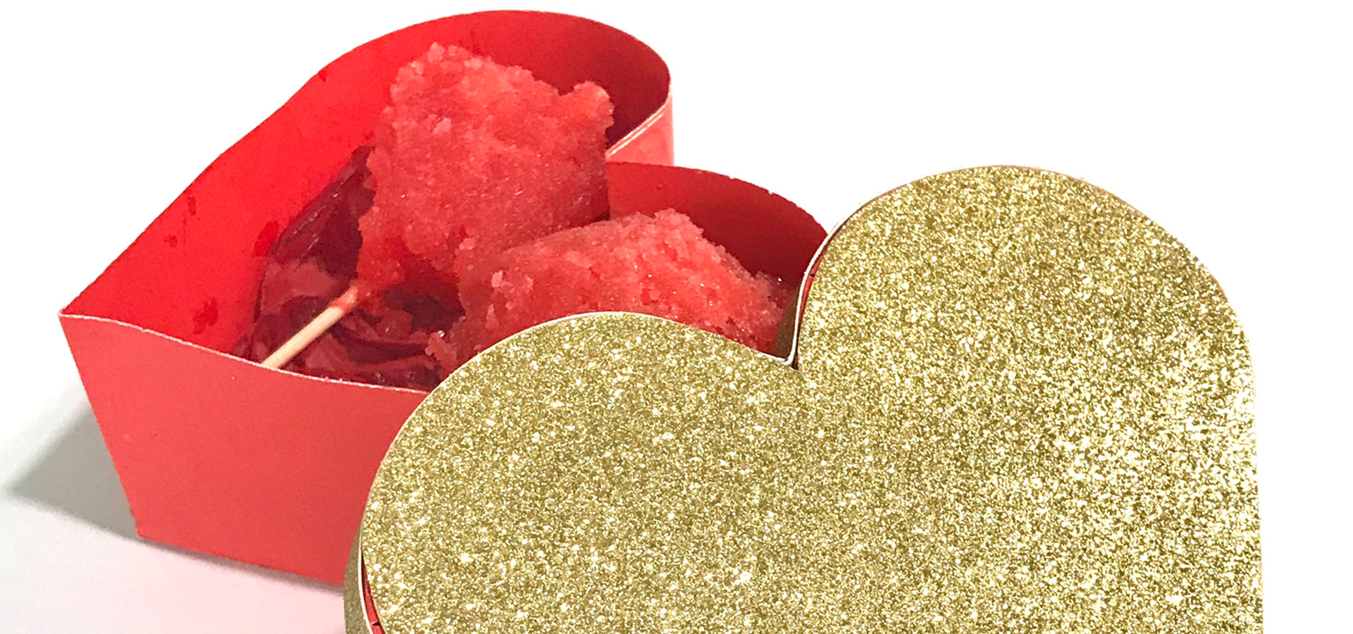 A heart-shaped red box with a gold glitter top