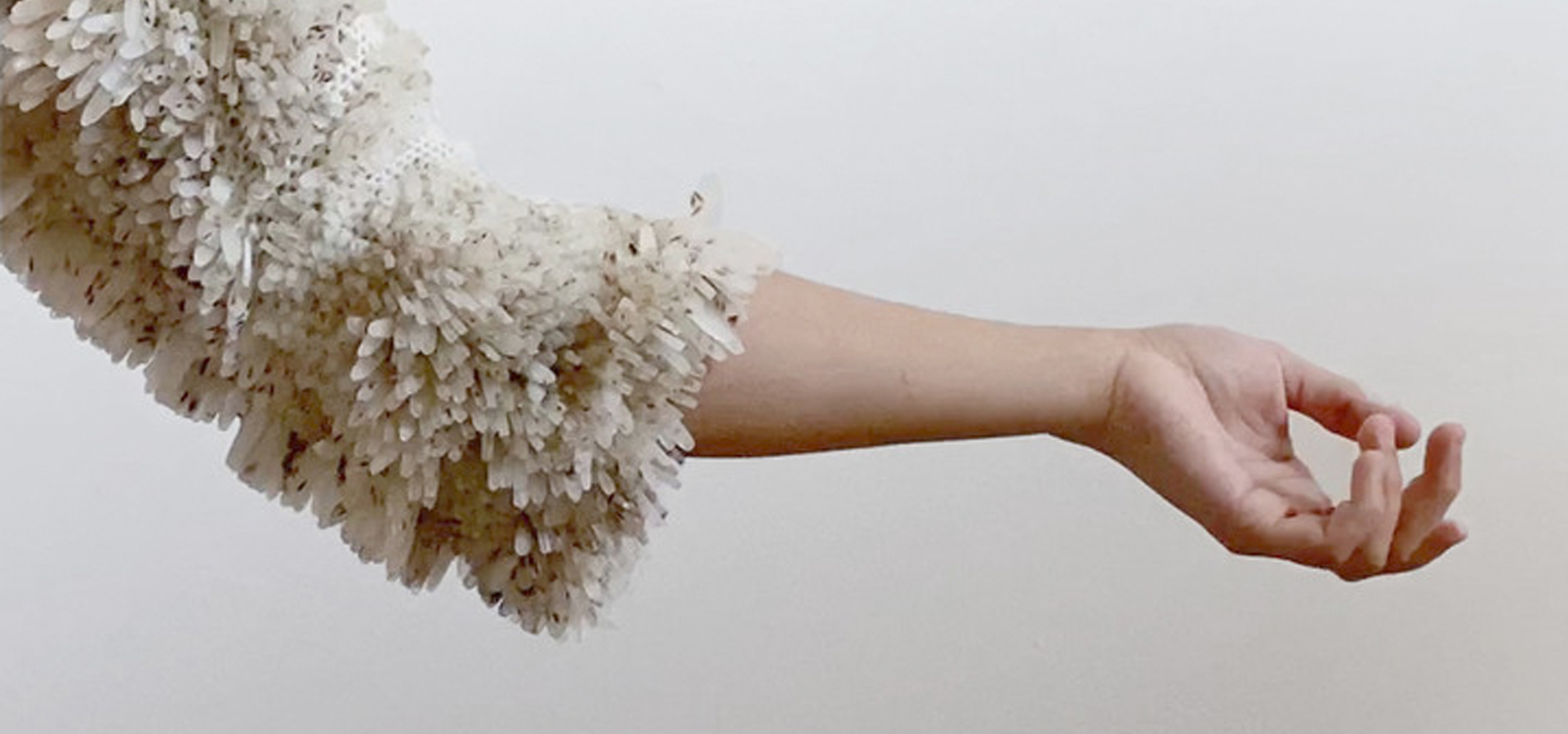 A person's arm, who is wearing a hydroponic garment that is sprouting seeds.
