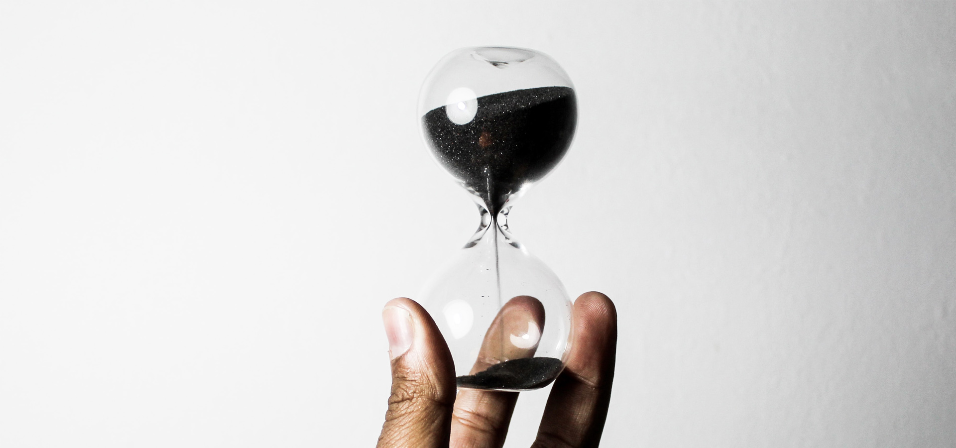 Hand holding an hourglass