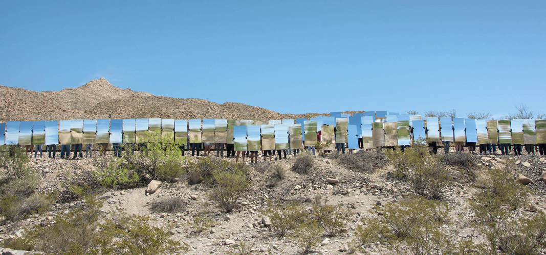 people in the desert holding up large scale mirrors.