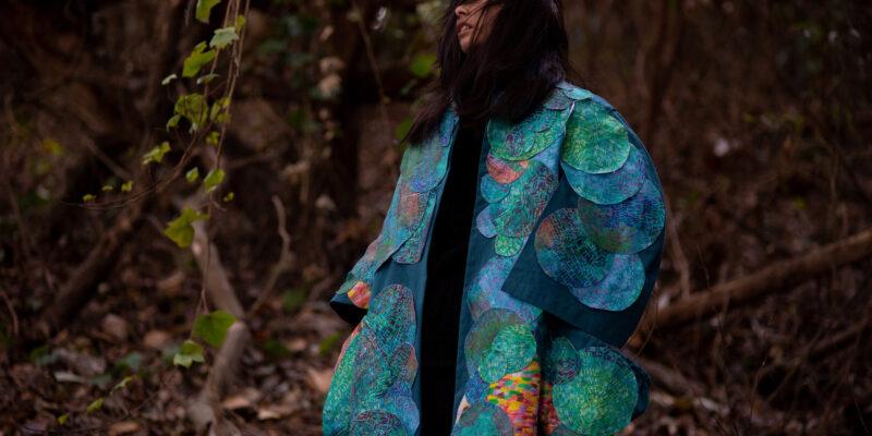 Female in woods modeling blue textile coat