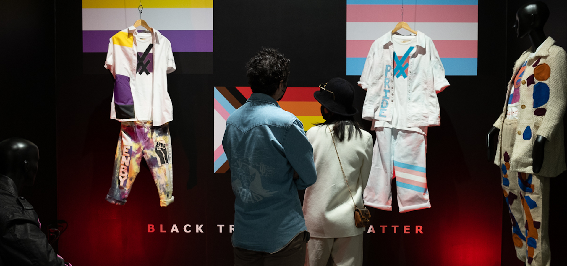 exhibition photo of outfits hanging in front of two people with their backs to the camera and multi-colored flags on the back wall