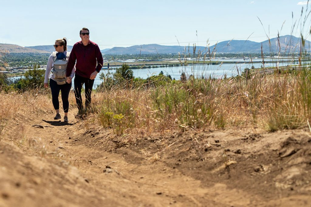 Man, woman, and baby hiking the Eulalona Trail, part of the Moore Park Trail System in Klamath Falls, Oregon.