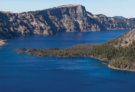 Wizard Island stands tall in the middle of the sparkling blue waters of Crater Lake National Park.