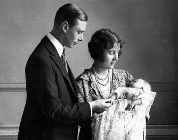 1926. The Duke and Duchess of York (later King George VI and Queen Elizabeth, the Queen Mother) pictured with their daughter (later, Queen Elizabeth II) as she sleeps in a precious christening robe, which has been used in the Royal Family for generations.