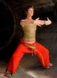 Woman in Asian Yoga Qigong influenced pose in a rust cylinder.