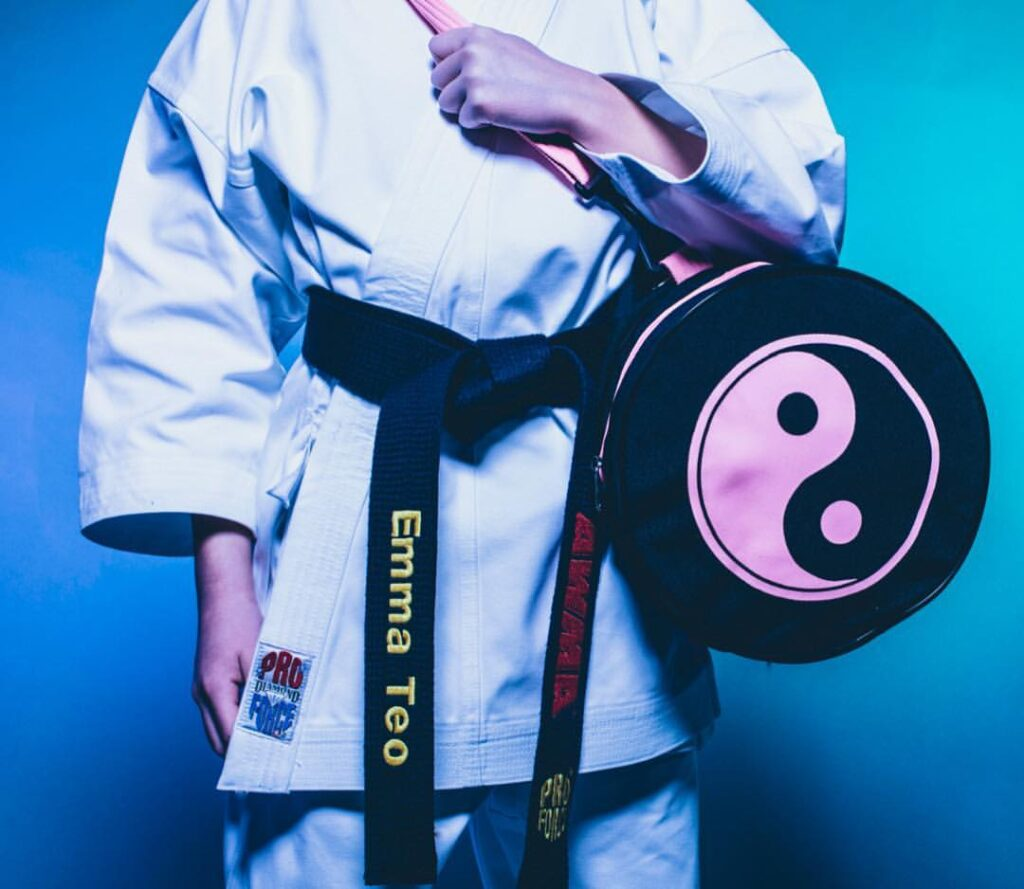 a torso wearing a white karate gi. the person is holding a black gear bag with a pink yin and yang printed on it. they're wearing a black belt that is embroidered with the AWMA logo and their name.