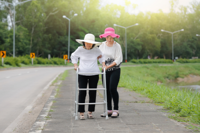 young woman helping a senior woman to walk