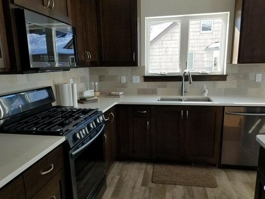 kitchen with black stove and window above the sink