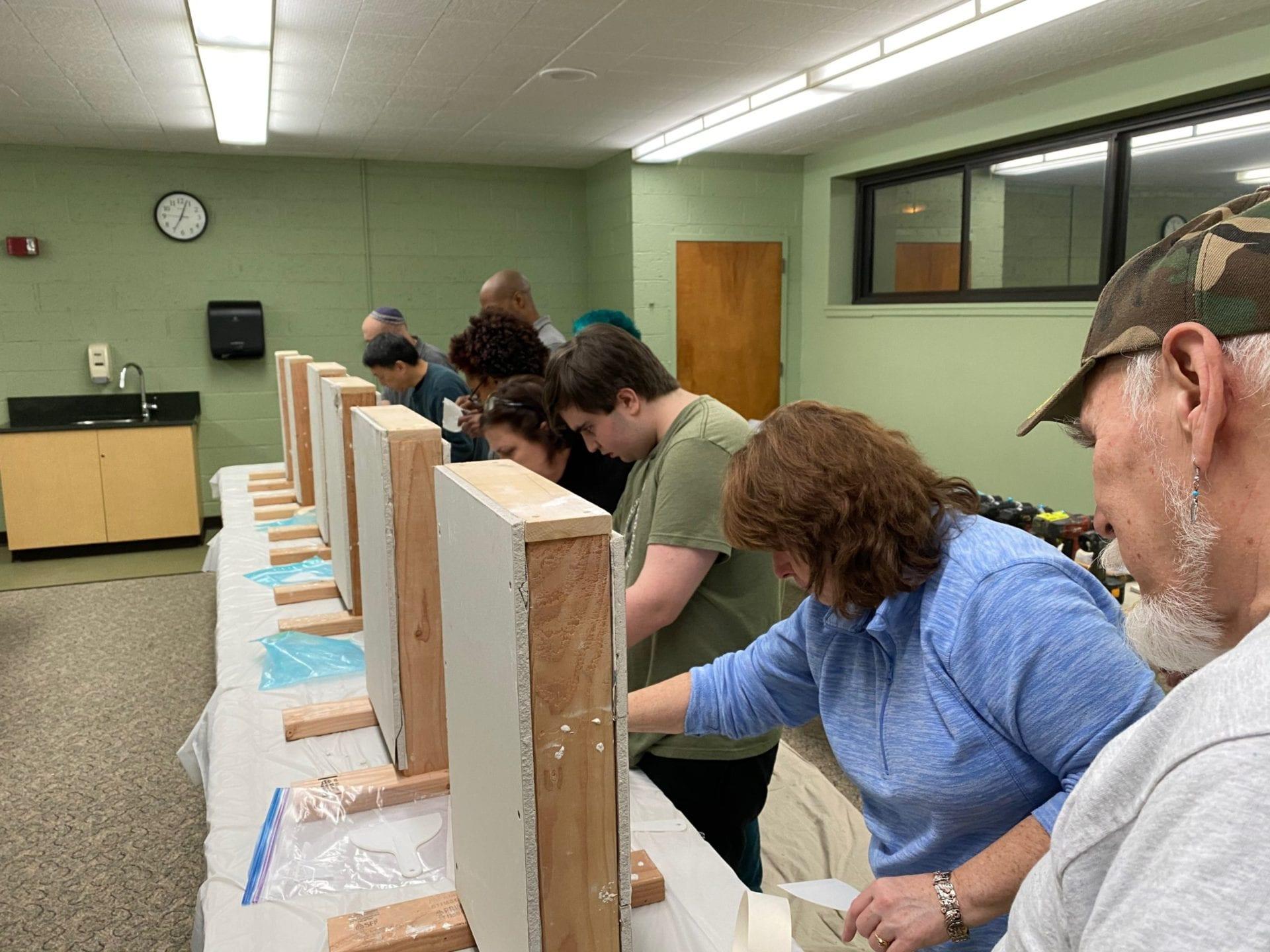 Students working on the wall repair workshop in freeport memorial library