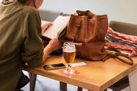 Woman reading and drinking beer