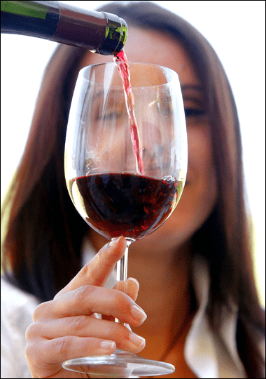 Glass of homemade wine that was bottled.