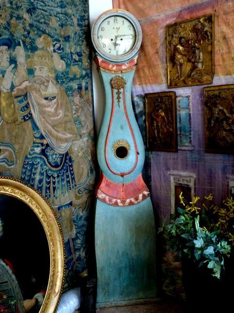 Image of an antique painted Mora clock surrounded by decorative antiques