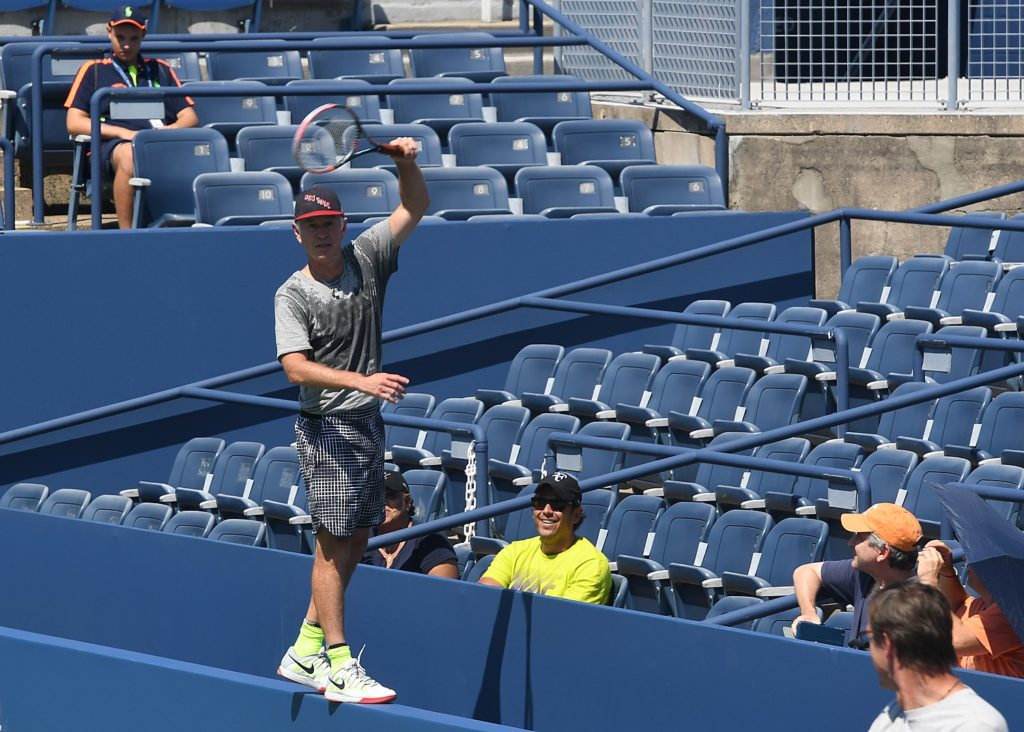 Tennis legend John McEnroe leaps onto the narrow railing in the seats to reach a ball, showing he still has it © 2016 Karen Rubin/news-photos-features.com