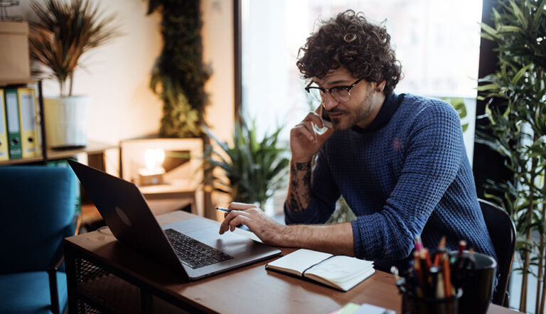 BGR informatique | Jeune homme au téléphone devant son ordinateur portable en télétravail