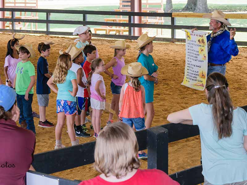 Children in horse arena with Man in Cowboy hat holding sign