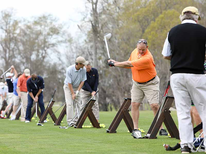 Golfers swinging on driving range