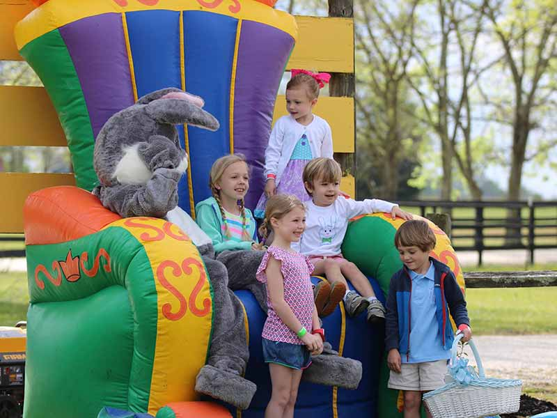 Children sitting with Easter bunny on large inflatable chair