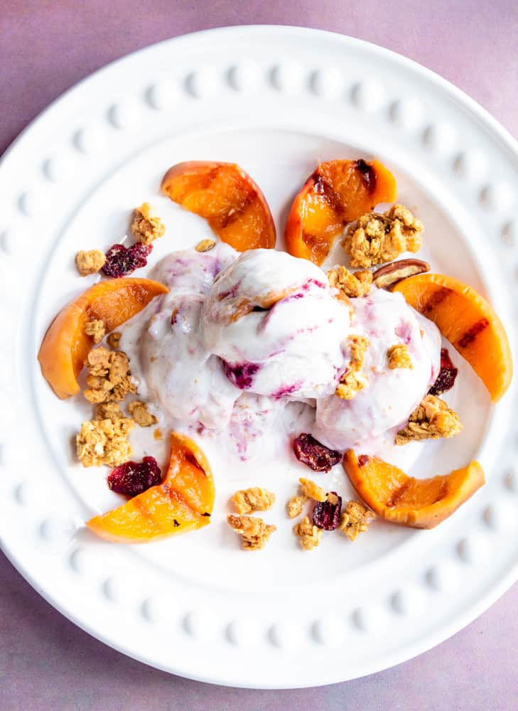 Grilled peaches and So Delicious Ice cream on a white plate,