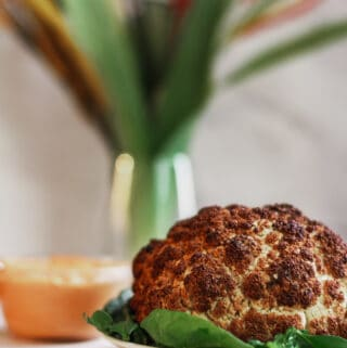 whole roasted cauliflower with spinach and harissa dipping sauce on white plate