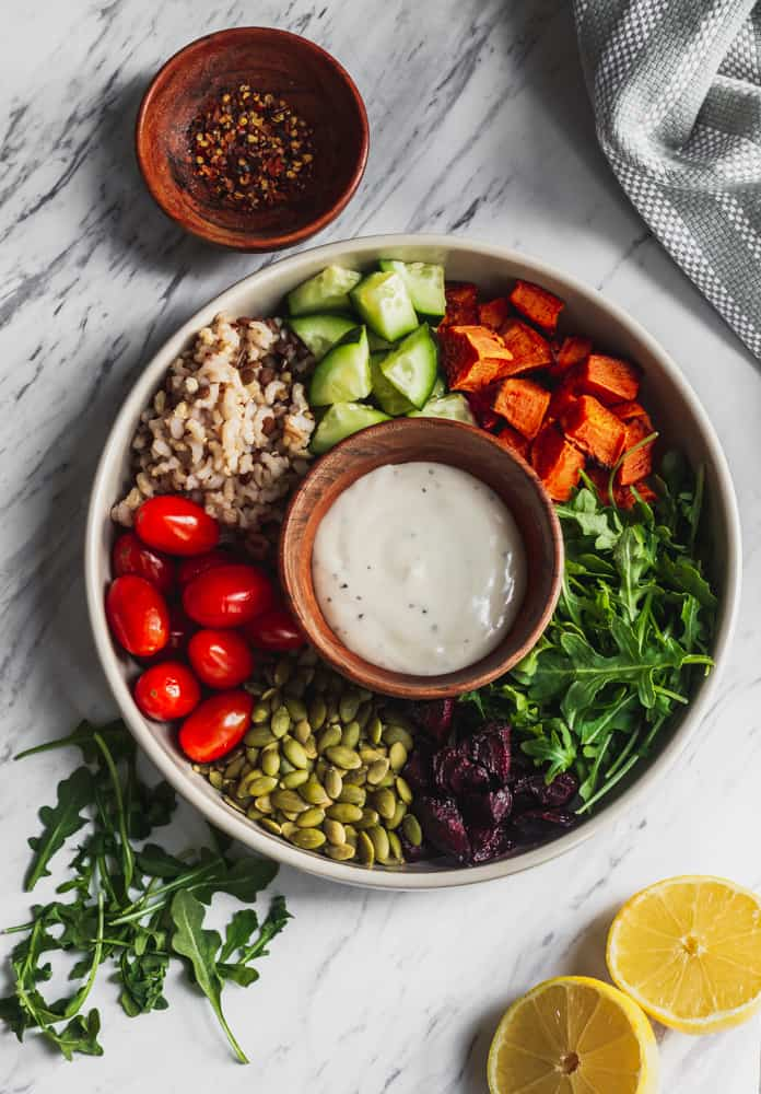 vegan salad recipe in tan bowl filled with sweet potatoes, tomatoes, roasted beets, greens and wild rice