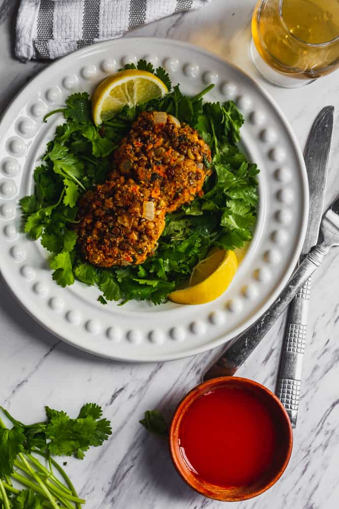 lentil patties on white plate with greens and lemons