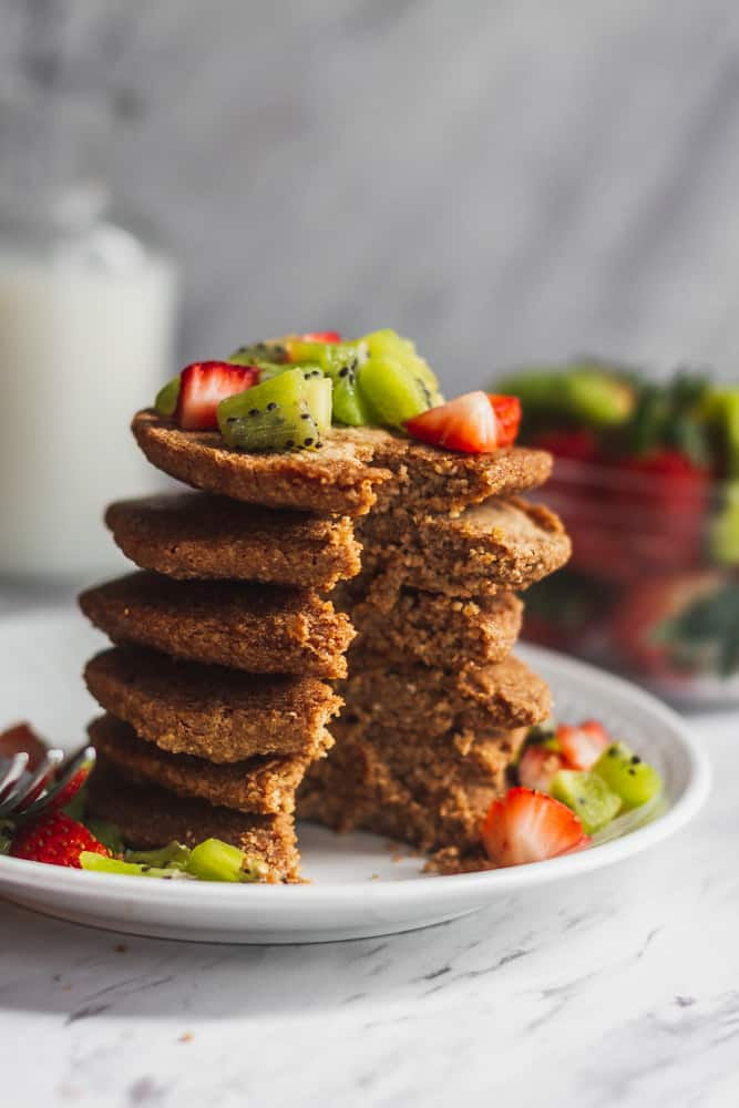 3 ingredient vegan oatmeal pancakes on white plate with strawberries and kiwi