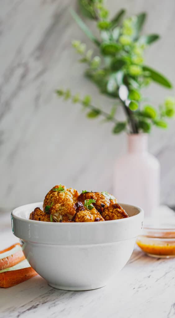 vegan buffalo sauce for cauliflower wings with cilantro, carrots, and celery