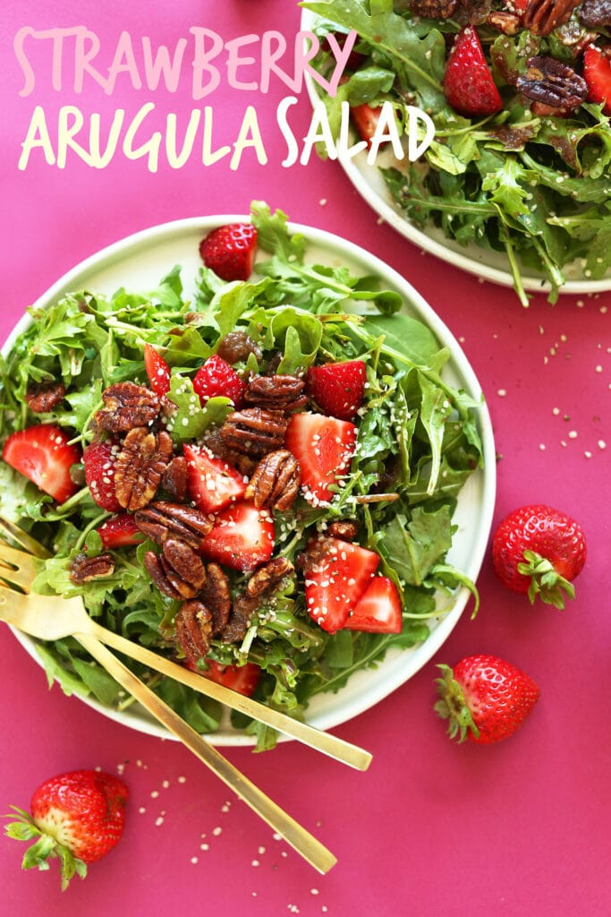 arugula salad with candied pecans, strawberries, hemp seeds on white plate